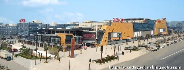 B区为广州白云万达广场的主体——大型综合购物中心。为了与万达集团A级店项目的定位相符合,从万达传统的购物中心里面组织方式中提取经典设计元素,用崭新的手法、材料和工艺来进行解构和重组。在白云万达购物中心的外立面设计中,采用了诸如金色铝单板、进口陶板及陶百页、定制金属网格等集团从未使用过的新型建材和高档建材,展现了商业综合体形象设计的全新可能性。在面向云城东路的商业主立面设计中,以金色金属板材和灰色亚光陶板之间强烈的色彩和质感对比造成了极具个性的雕塑感体块,给了商业综合体面向城市的整体